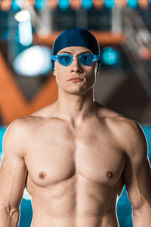 handsome muscular swimmer in swimming cap and goggles