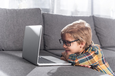 little boy looking at laptop at home while leaning on couch Banco de Imagens