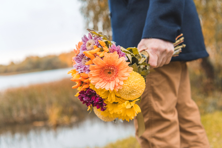 cropped view of man holding bouquet of autumn flowers Stock Photo
