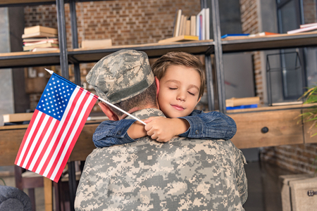 military father and son with usa flag embracing Stock Photo