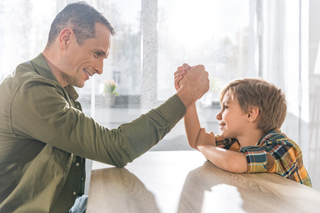side view of father and little son arm wrestling together at home
