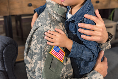 cropped shot of embracing military father and son