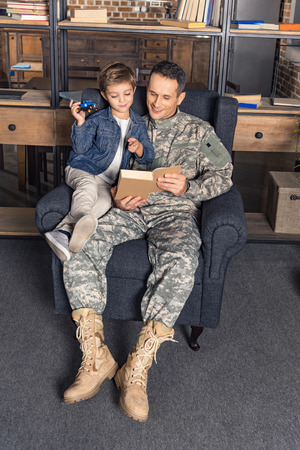 father in military uniform and son reading book together in armchair