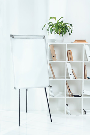 empty flipchart and wooden shelves with folders in office Stock Photo