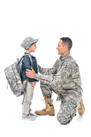father in camouflage uniform and son with backpack and cap isolated on white