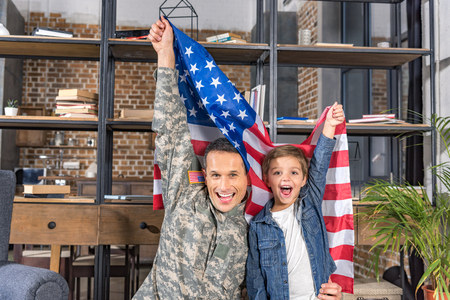 happy father in army uniform and son with big usa flag at home Stock Photo
