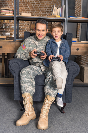military father and little son playing console with gamepads at home in armchair