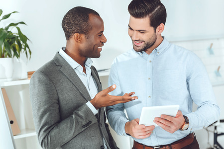 smiling african american and caucasian businessmen talking on office and using tablet