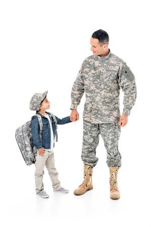 Niño y padre en uniforme militar tomados de la mano juntos aislado en blanco