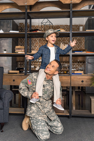 happy little son riding on military father shoulders at home Stock Photo