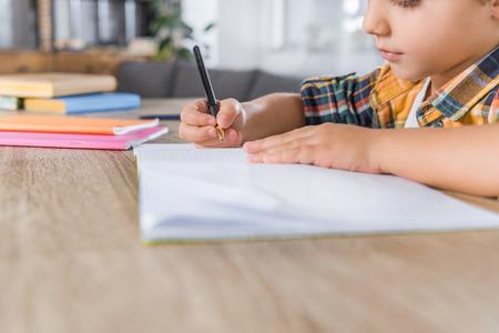 close-up shot of little schoolboy doing homework