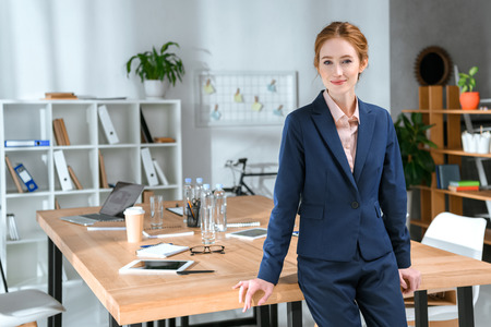 smiling businesswoman leaning on table at office space and looking at camera