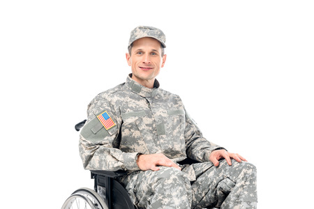 smiling military man in wheelchair isolated on white