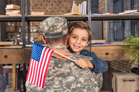 military father and happy little son with usa flag embracing