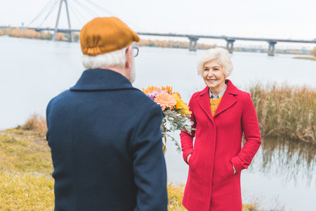 senior husband gifting bouquet of flowers to his wife  Stock Photo
