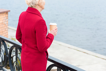 cropped view of senior woman in red coat with coffee to go on quay