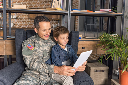 military father and son using tablet together while sitting in armchair Stock Photo