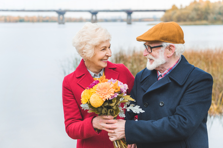 happy senior couple with bouquet of flowers standing at autumn lake