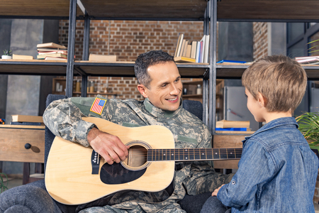 handsome smiling military man playing guitar for little son