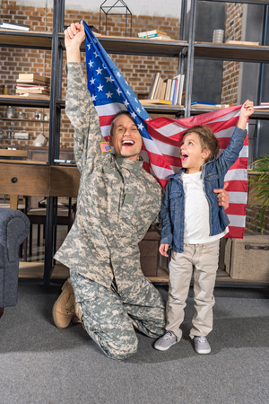handsome father in army uniform and son with big usa flag at home