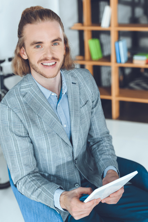 overhead view of smiling businessman sitting in chair with tablet Stock Photo