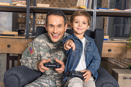 portrait of happy father in military uniform and son playing video game together at home