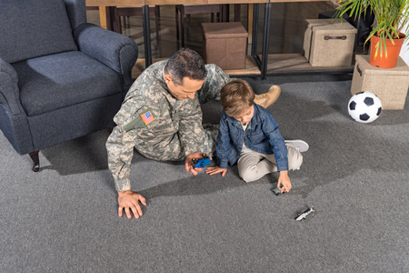 military father and son playing with toys while sitting on floor at home Stock Photo
