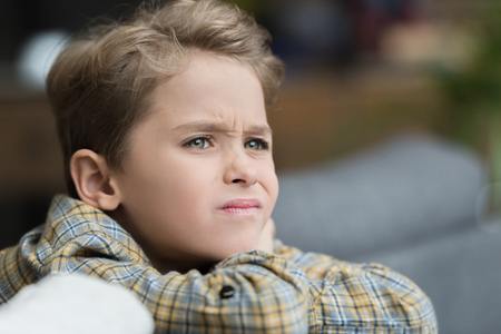 Portrait of little boy making a grumpy face while looking aside