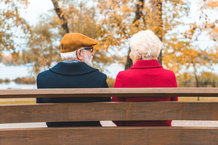 back view of senior couple sitting on bench in autumn park