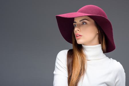 attractive woman posing in burgundy felt hat, isolated on grey