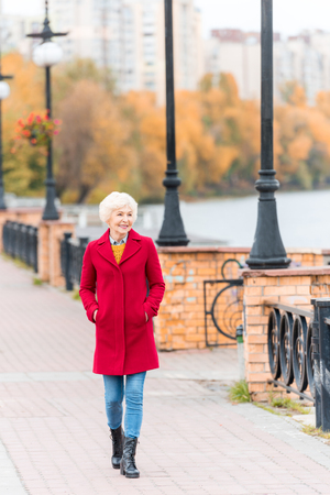 senior smiling woman in red coat walking on quay