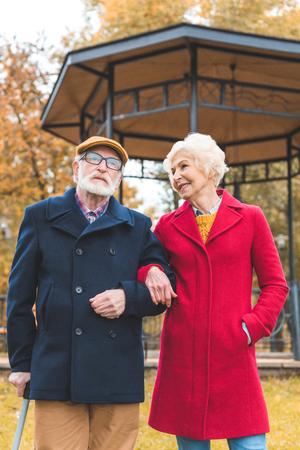 smiling senior couple walking in autumn park with gazebo on background