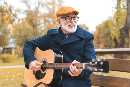 cheerful stylish senior man playing on acoustic guitar in autumn park Фото со стока