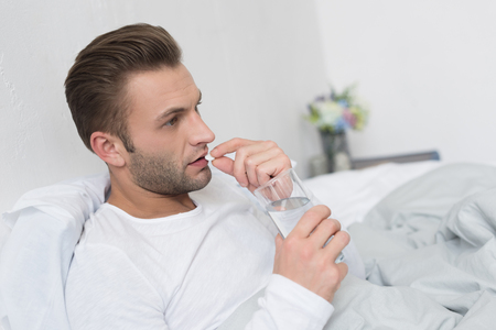 Young handsome man sitting in bed while taking a pill and holding glass of water