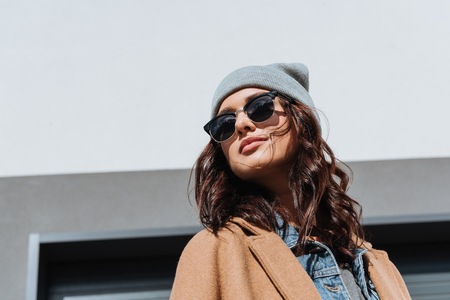 Portrait of beautiful woman in autumn outfit and black sunglasses standing outside