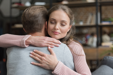 Young attractive woman embracing her husband with eyes closed