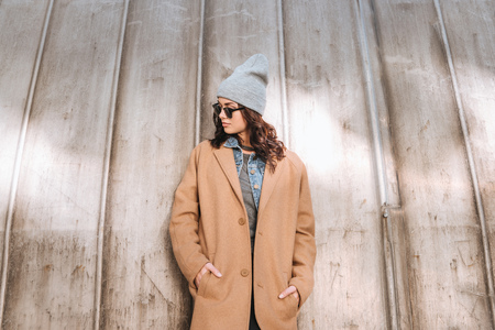 Stylish woman in autumn outfit and black sunglasses standing outside and looking down Фото со стока