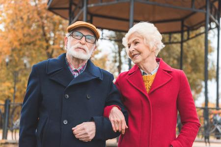 happy senior couple walking in autumn park with gazebo on background
