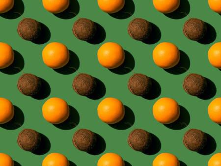 pattern with fresh ripe oranges and coconuts with shadows on green