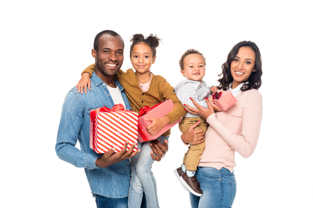 happy african american family holding presents and smiling at camera isolated on white