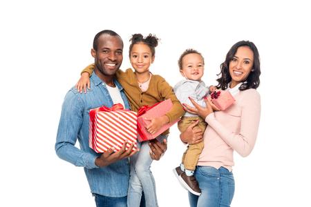 Heureuse famille afro-américaine tenant des cadeaux et souriant à la caméra isolée sur blanc