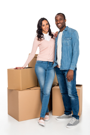 happy african american couple standing with cardboard boxes and smiling at camera isolated on white Archivio Fotografico - 102653270