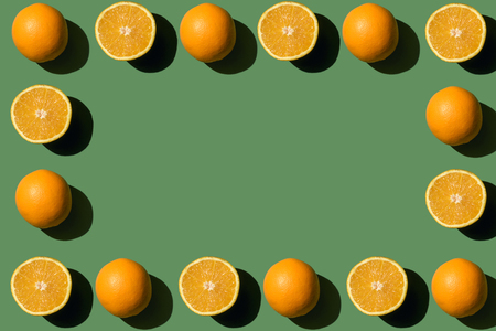 top view of frame made from fresh ripe whole and sliced oranges on green