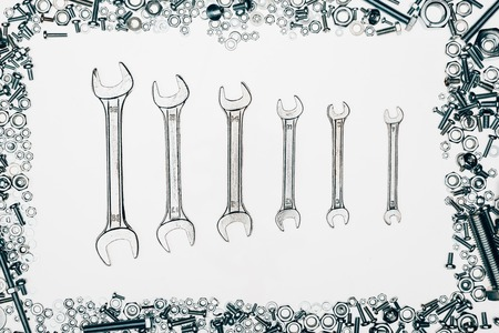 top view of metal wrenches, various bolts and framing nails isolated on white