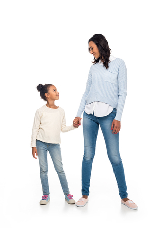 beautiful happy african american mother and daughter holding hands and smiling each other isolated on white