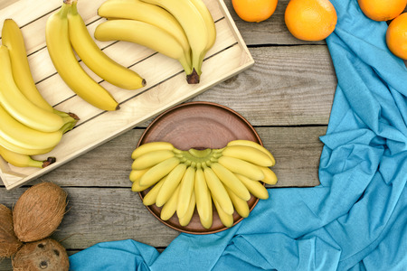 top view of fresh ripe bananas, oranges and coconuts on wooden table top