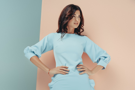 Stylish woman standing in fashionable turquoise dress looking away