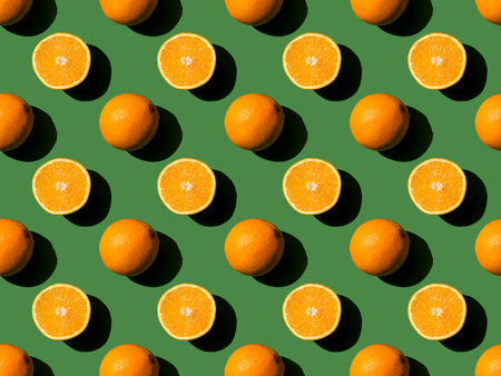 top view of ripe fresh whole and halved oranges on green