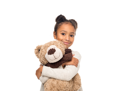 beautiful african american child hugging teddy bear and smiling at camera isolated on white