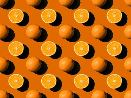 top view of ripe fresh whole and halved oranges on orange Standard-Bild